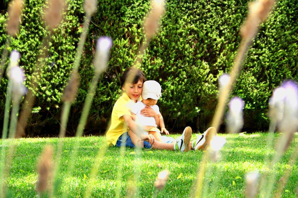 Download Free Stock HD Photo of Sweet older brother hugging his young sister on the grass Online