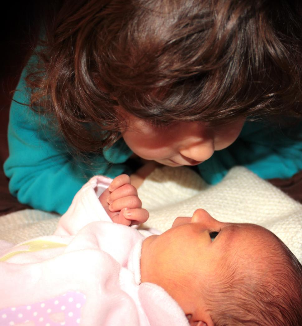 Download Free Stock HD Photo of Toddler looking her younger baby sister in the eyes Online