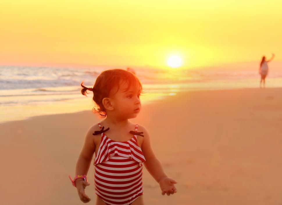Download Free Stock HD Photo of Little girl on the beach at sunset - Summer vacations Online