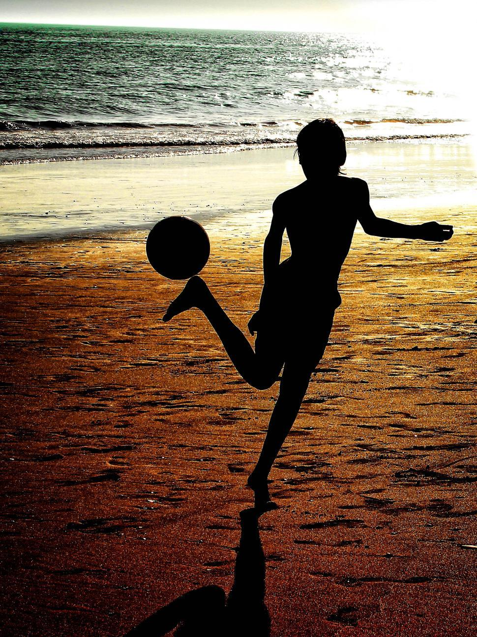 Download Free Stock HD Photo of Silhouette of a boy playing soccer at the beach - Grunge burned  Online