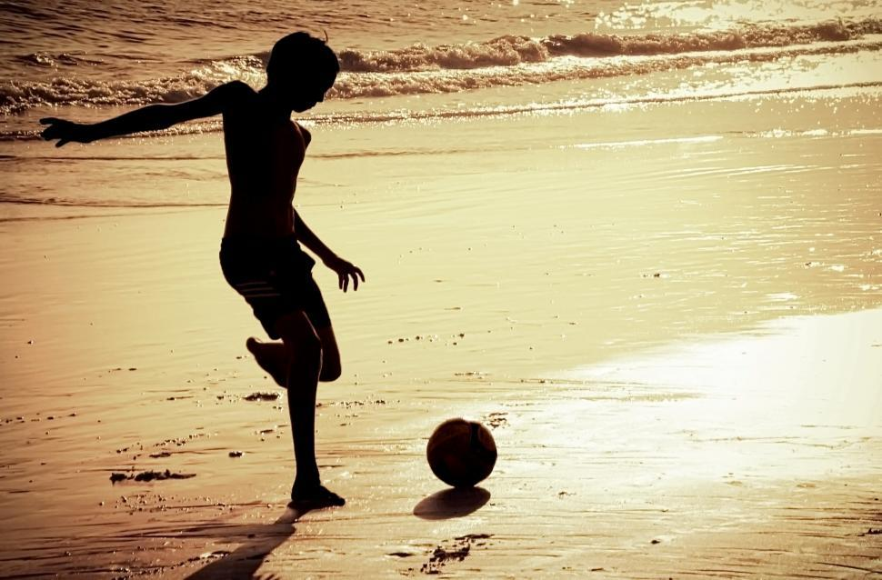 Download Free Stock HD Photo of Silhouette of boy on the beach playing football Online