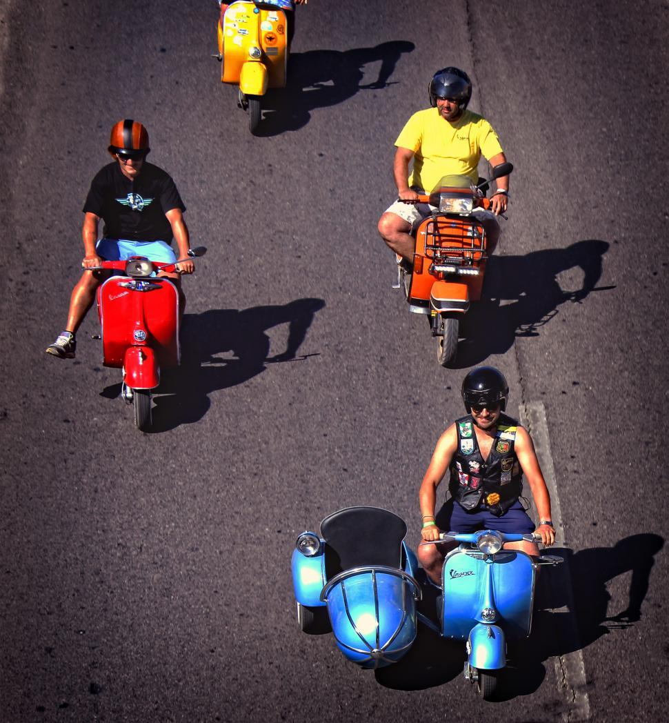 Download Free Stock HD Photo of  Colorful group of bikers riding vintage italian scooters. Edito Online