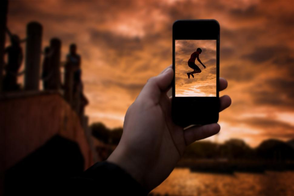 Download Free Stock HD Photo of Taking a photo with smartphone - Happy boy jumping into river Online