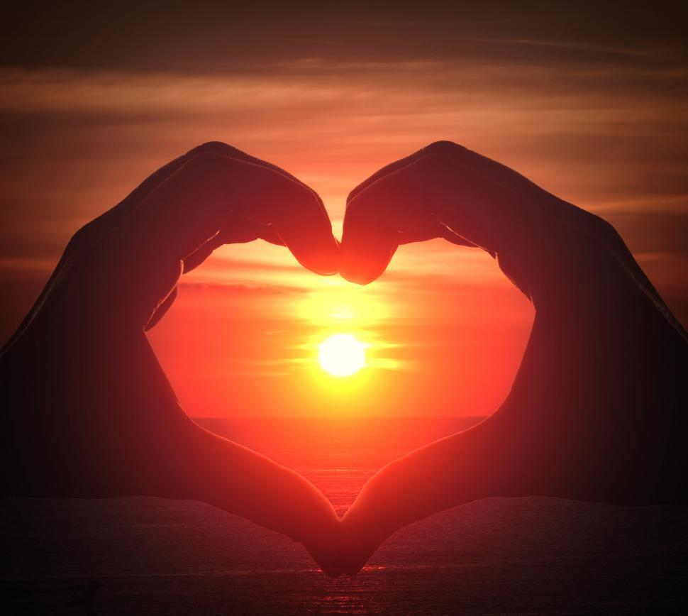 Free image of Hand silhouette in heart shape with sunset in the middle and ocean background