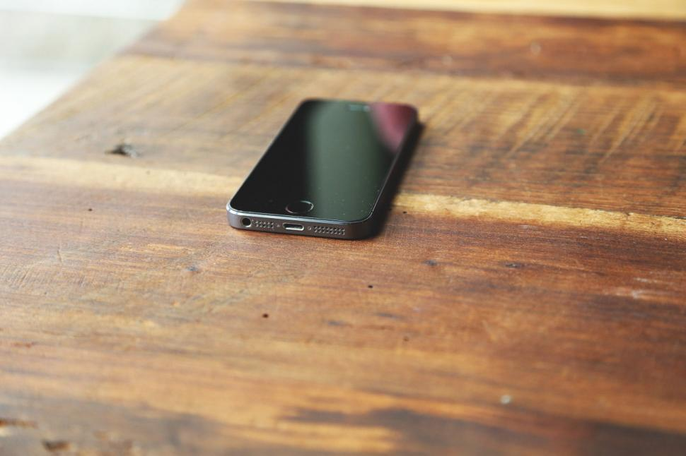 Download Free Stock HD Photo of Phone sits on table Online