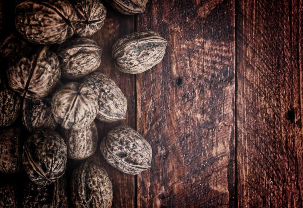 Download Free Stock HD Photo of Whole walnuts on rustic old wooden table Online