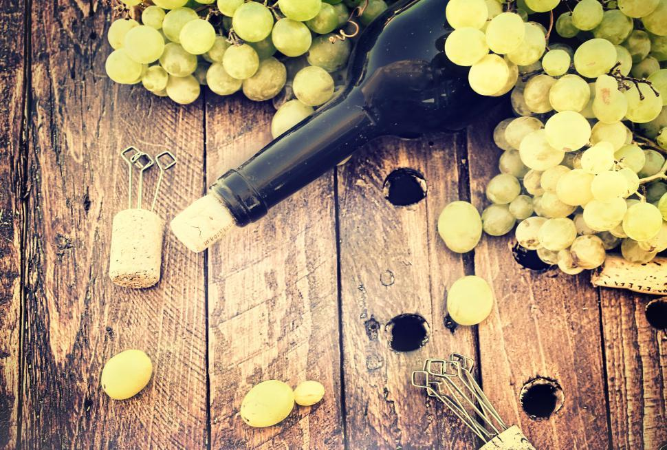 Download Free Stock HD Photo of Bottle of wine with grapes and corks on wooden table - Rustic loo Online