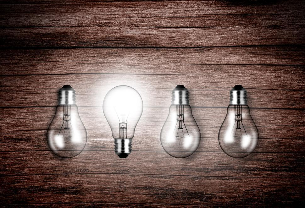 Download Free Stock HD Photo of Lightbulbs on wood - A glowing lightbulb contrasts with others a Online