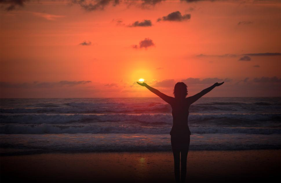 Free image of Celebrating life - A woman raises her arms at sunset on a deserted beach