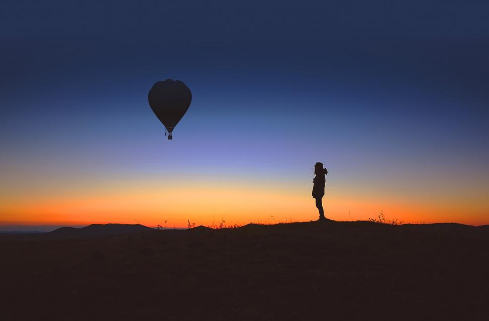 Download Free Stock HD Photo of A lone person observes an hot air balloon at sunrise Online