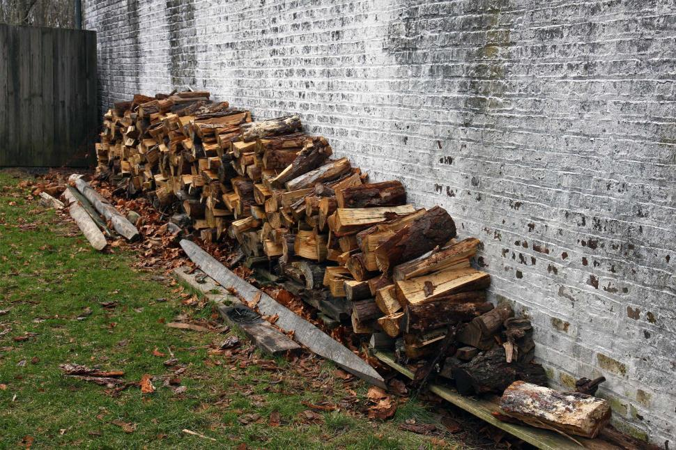 Download Free Stock HD Photo of Woodpile Against The Side Of A House Online