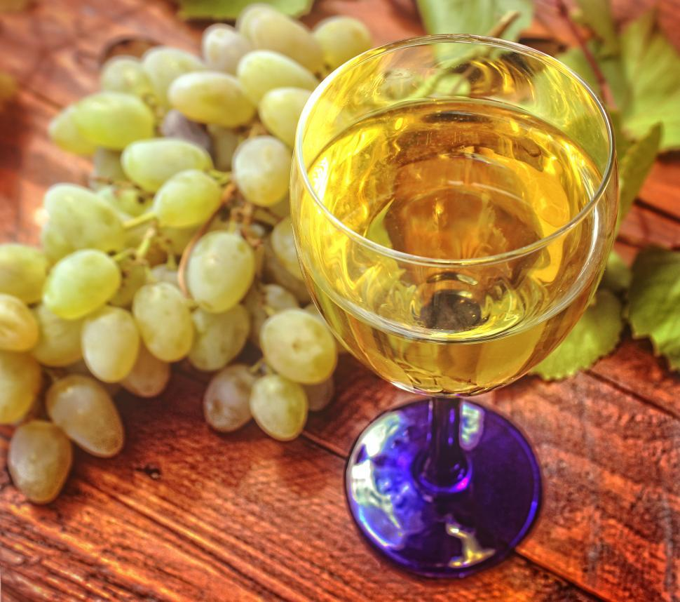 Download Free Stock HD Photo of Glass of white wine and a bunch of grapes in the background Online