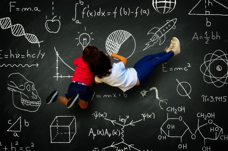 Download Free Stock HD Photo of Two little girls writing on a blackboard with science subjects Online