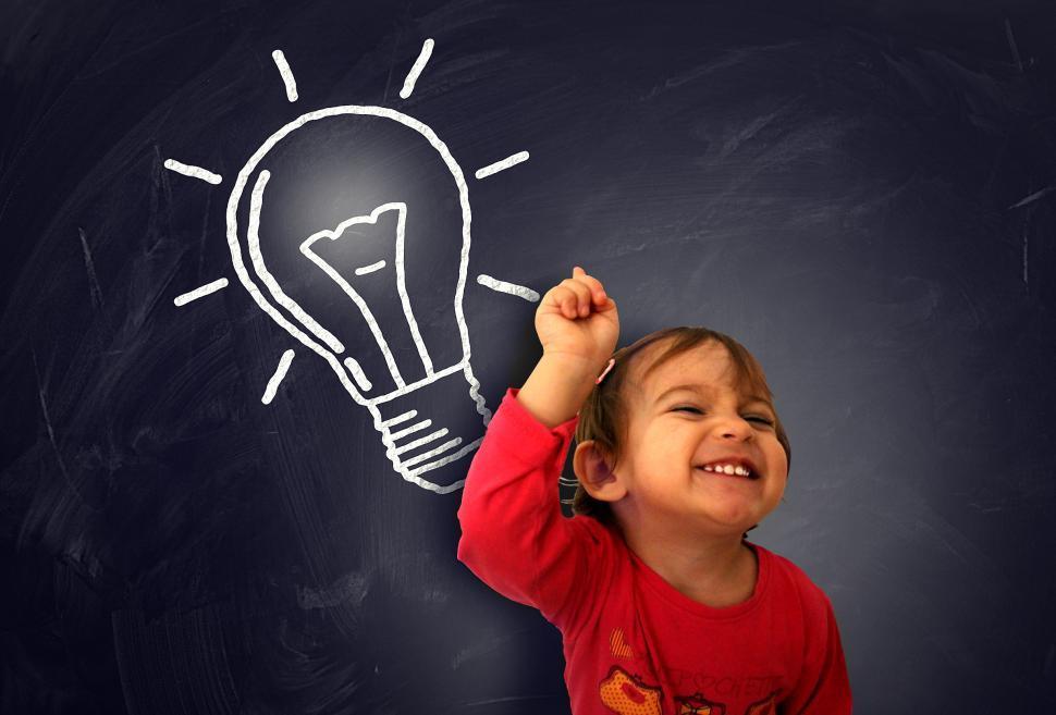 Download Free Stock HD Photo of Little cute girl having a good idea on the blackboard - Learning Online
