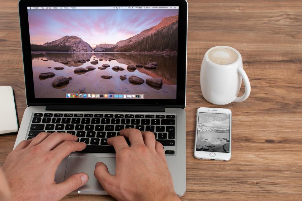 Download Free Stock HD Photo of Person working on a laptop computer with phone and coffee Online