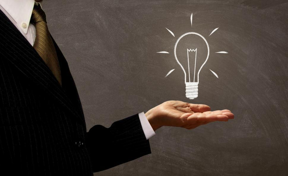 Download Free Stock HD Photo of Businessman Holding Light Bulb on Chalkboard Online
