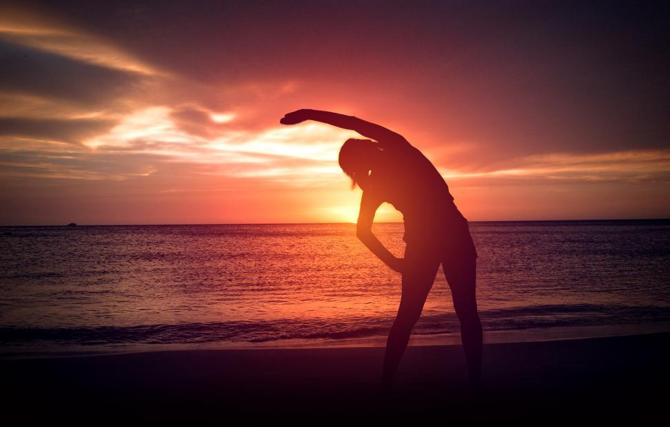 Download Free Stock HD Photo of Silhouette of Young Woman - Warm-Up exercise on the Beach at Sun Online