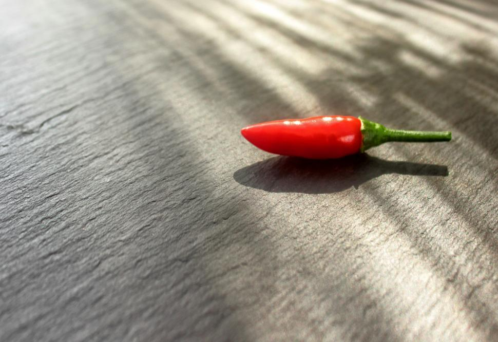 Download Free Stock HD Photo of Red Chilli Pepper Isolated on Stone Background Online