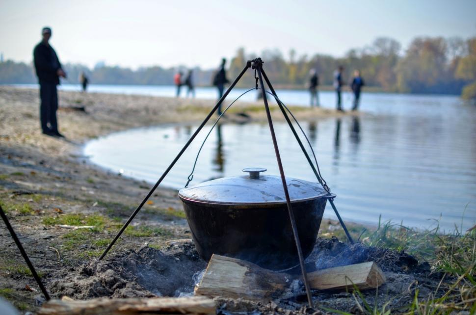 Download Free Stock HD Photo of Cooking food in nature against the backdrop of the river with fishermen  Online