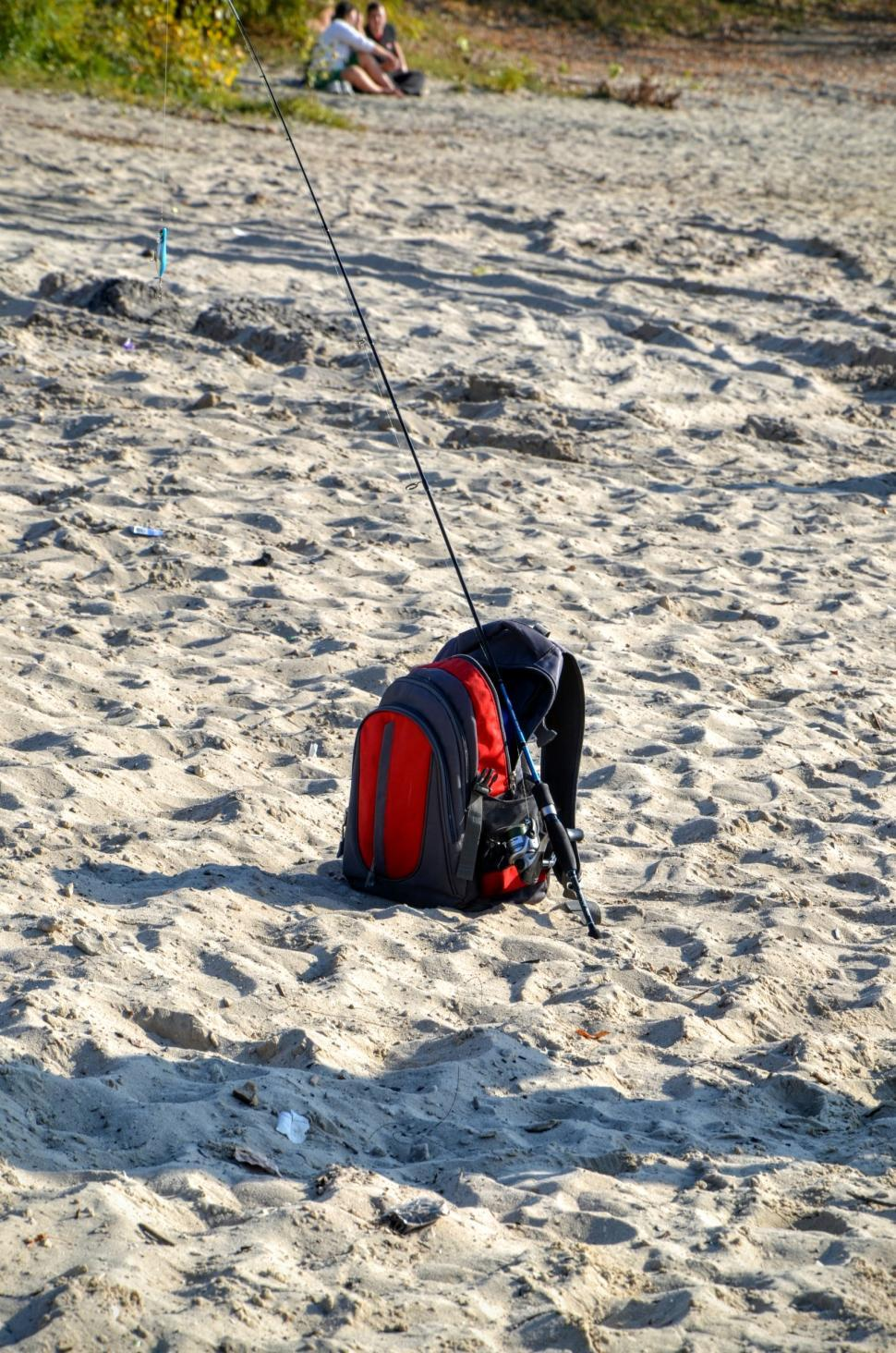 Download Free Stock HD Photo of Fisherman's bag with spinning rod lies on the sand on the shore of the river  Online