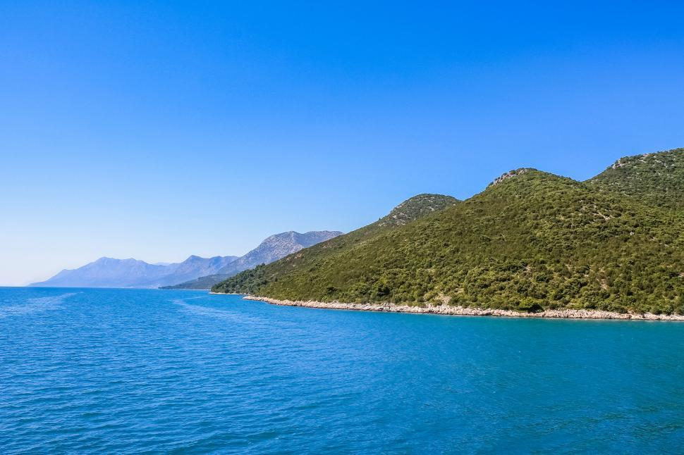 Free image of The beautiful croatian coast seen from the water, with green hills and blue water. Clear blue summer sky.