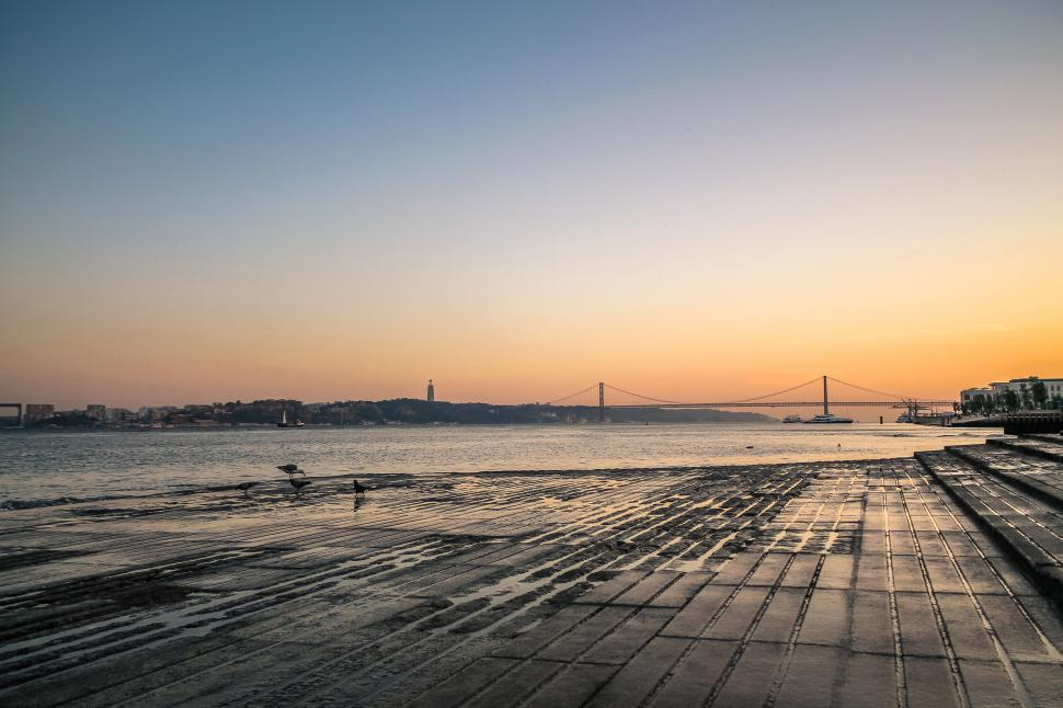 Free image of Beautiful summer sunset in Lisbon with the Abril Bridge and Christ the King statue in the background. Traveling Europe.