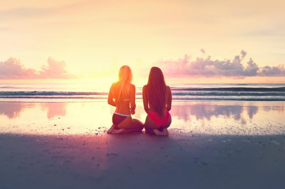 Download Free Stock HD Photo of Two Young Women Watching the Sunset Over the Ocean Online