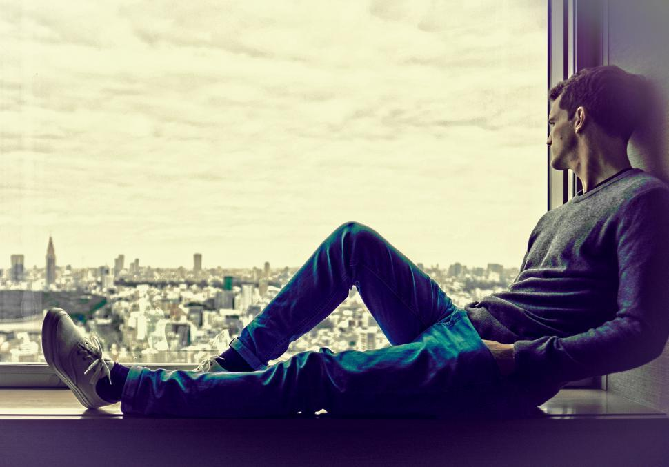 Download Free Stock HD Photo of Young Man Enjoying the City View at the Window - With Copyspace Online
