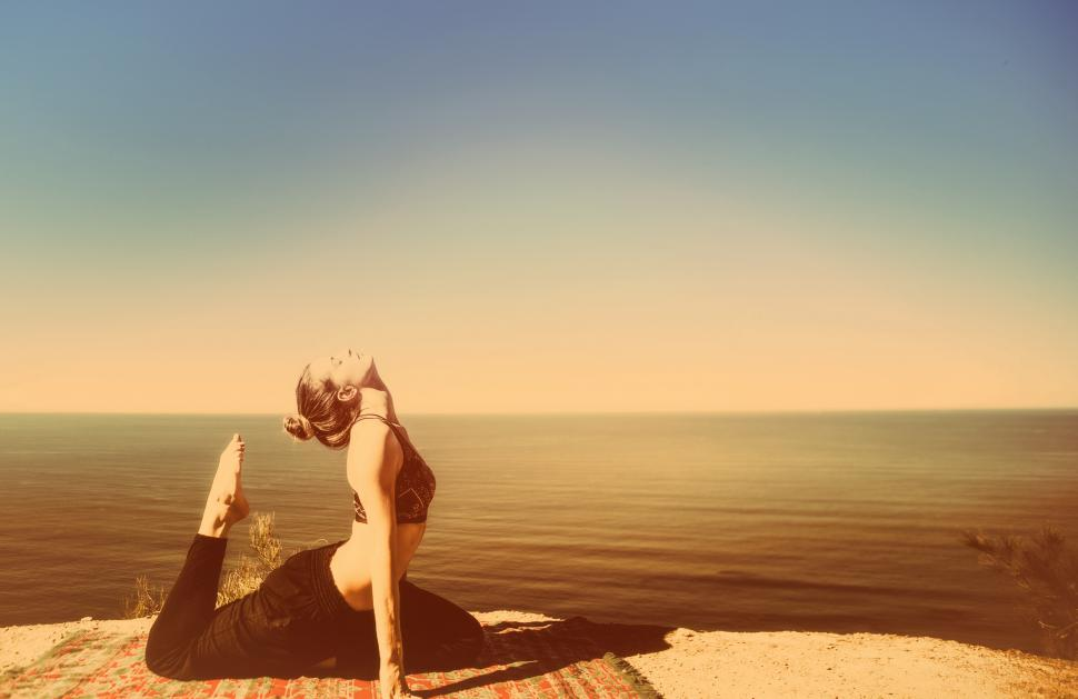 Download Free Stock HD Photo of Woman Practicing Yoga by the Ocean - Metal Toned Online