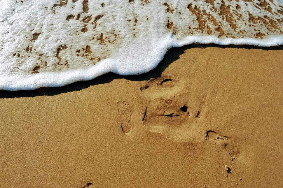 Download Free Stock HD Photo of The imprint of a bare foot on the sand near the sea with a running wave Online