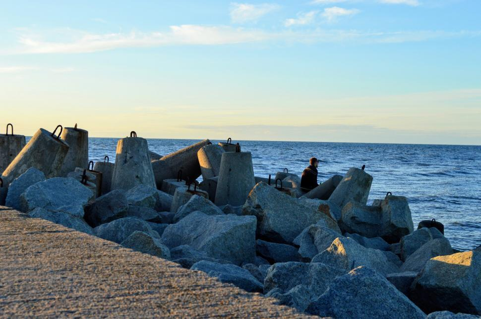 Download Free Stock HD Photo of A man sits among tetrapod breakwater on the Baltic Sea Online