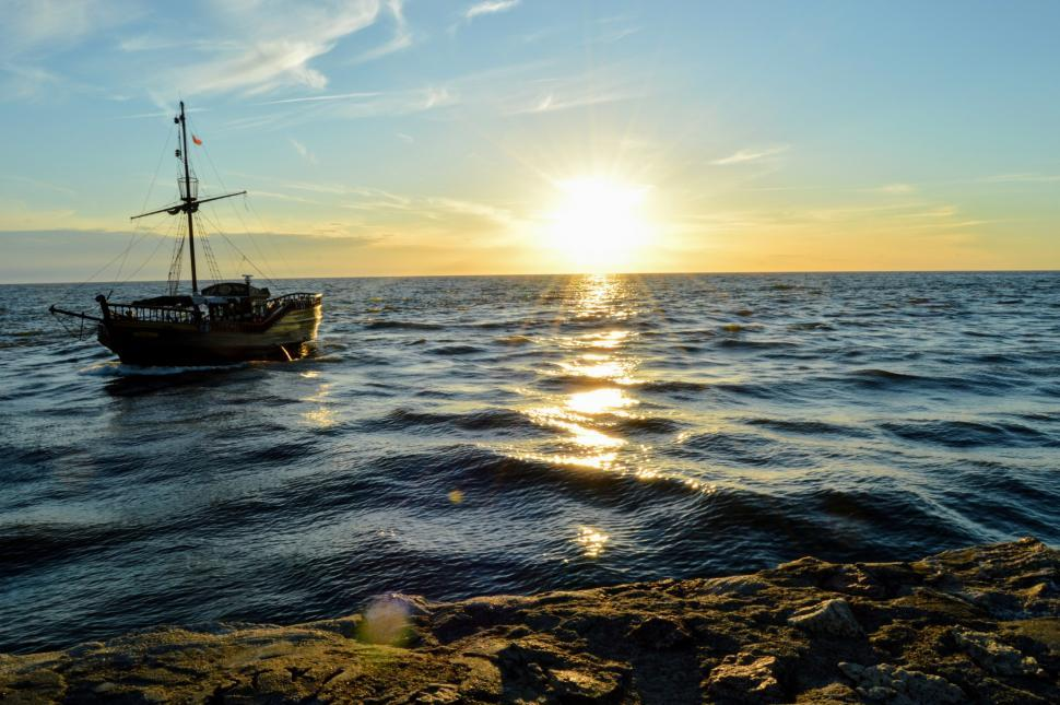 Download Free Stock HD Photo of Sailing ship floating in the sea against the backdrop of the setting sun Online