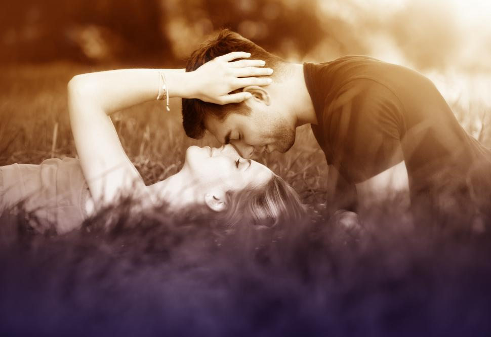 Download Free Stock HD Photo of Couple Kissing Laying on the Grass Online