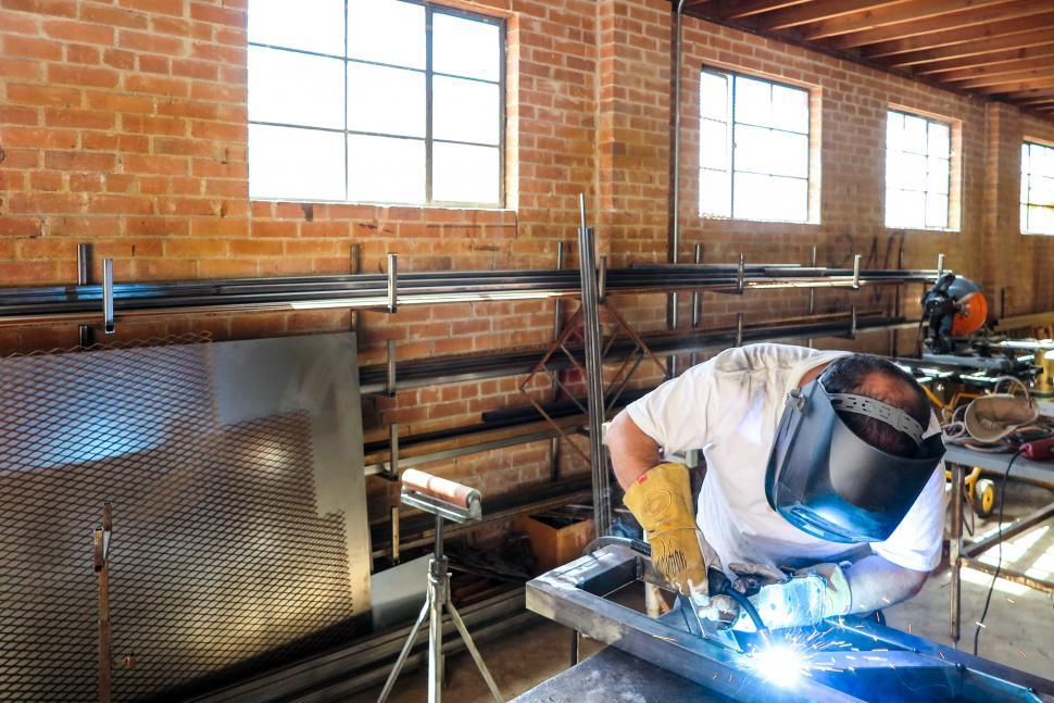 Download Free Stock HD Photo of Welder working in an industrial warehouse Online