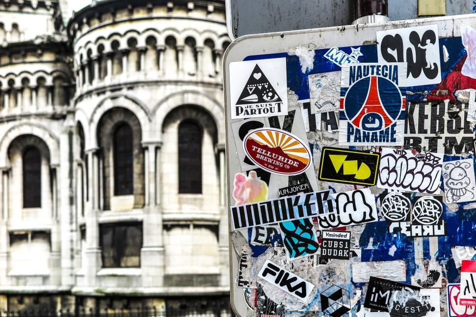 Free image of Paris street sign with so many stickers it s no longer legible. Sacre Coeur in the background.