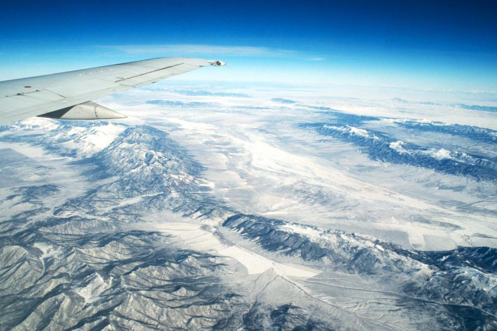 Free image of Looking out an airplane window at the mountains below