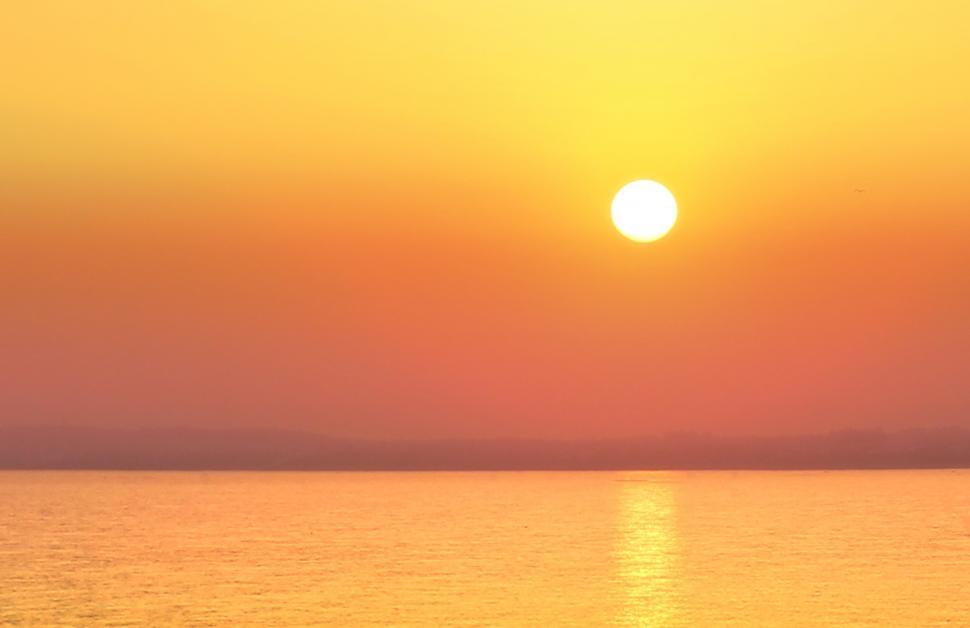 Download Free Stock HD Photo of Hazy Sunset Over a Calm Sea - Summer Holidays Online