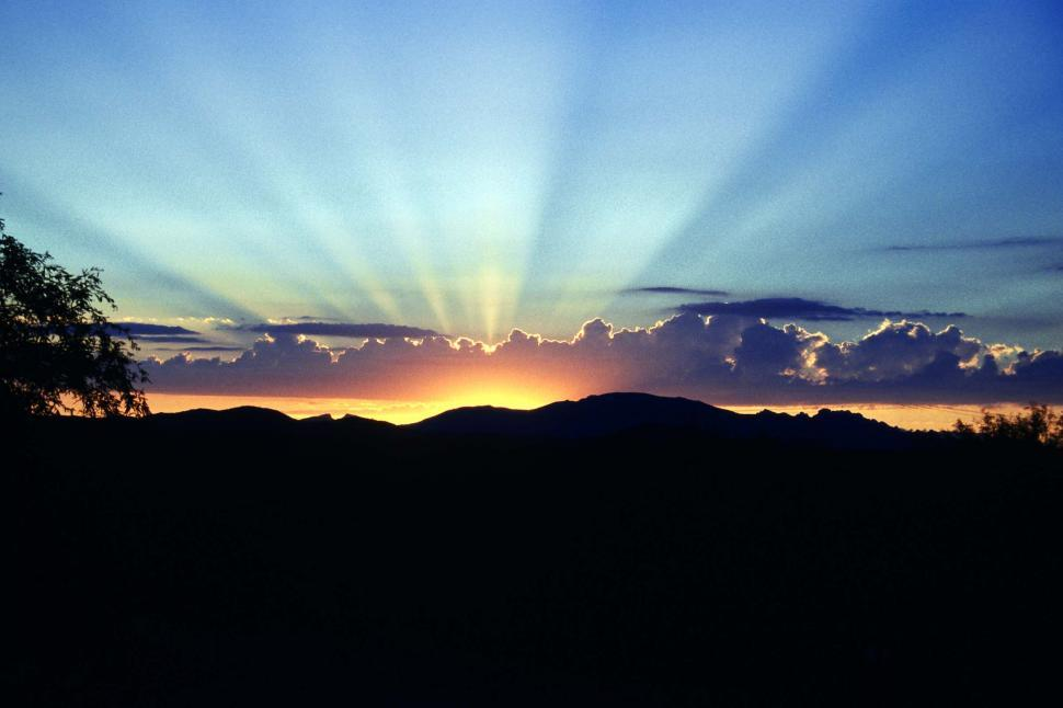 Free image of Sun setting over the mountains with rays of remaining sun shining. Graphically similar to the flag of Arizona.