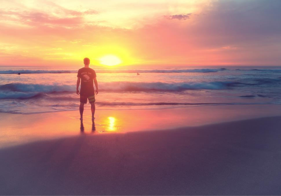 Download Free Stock HD Photo of Young Man at Sunset on the Beach Online