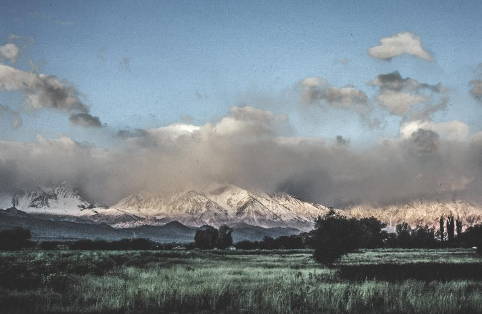 Download Free Stock HD Photo of Grainy film of Clouds over a snow mountain Online