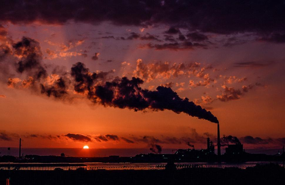 Download Free Stock Photo of Industrial factory smoke from smokestacks over sunset sky