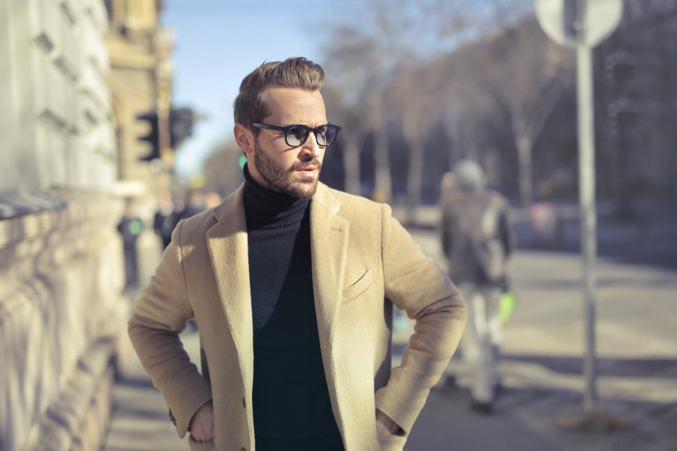 Download Free Stock HD Photo of Young Adult Man in long overcoat and sunglasses posing on the st Online