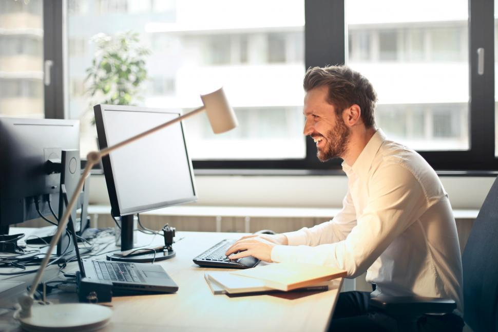 Download Free Stock Photo of Young Adult Man In White Shirt Smiling and Using a Computer