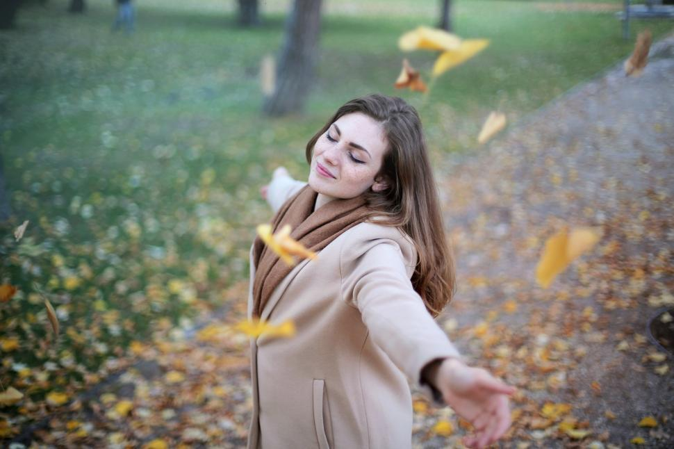 Download Free Stock Photo of Beautiful young adult woman playing among falling autumn leaves