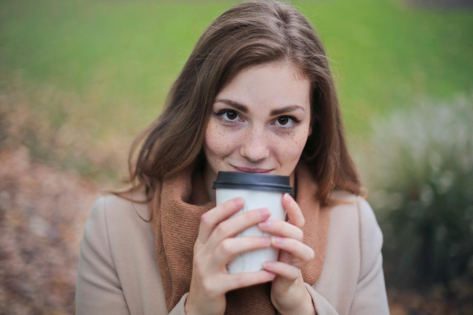 Download Free Stock Photo of Close-up of Young Woman in Brown Top and Scarf Holding a Disposa