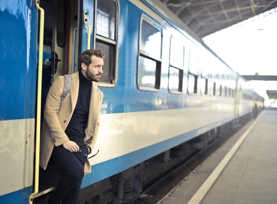 Download Free Stock Photo of Young Adult Man looks out of the open train door during a stop