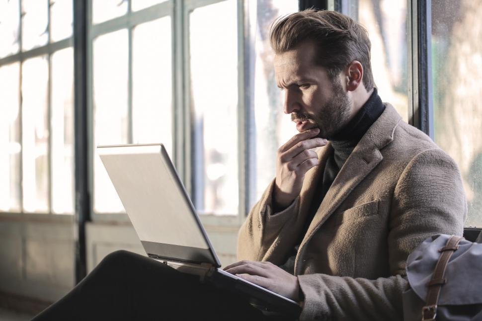 Download Free Stock HD Photo of Young Adult Man looking seriously on laptop screen while sitting Online