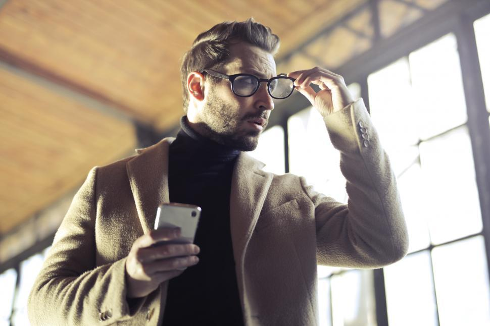 Download Free Stock HD Photo of Young Adult Man removing his glasses Online