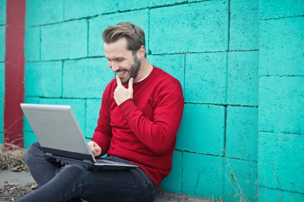 Download Free Stock HD Photo of Young Adult Man using a laptop against  turquoise brick wall Online