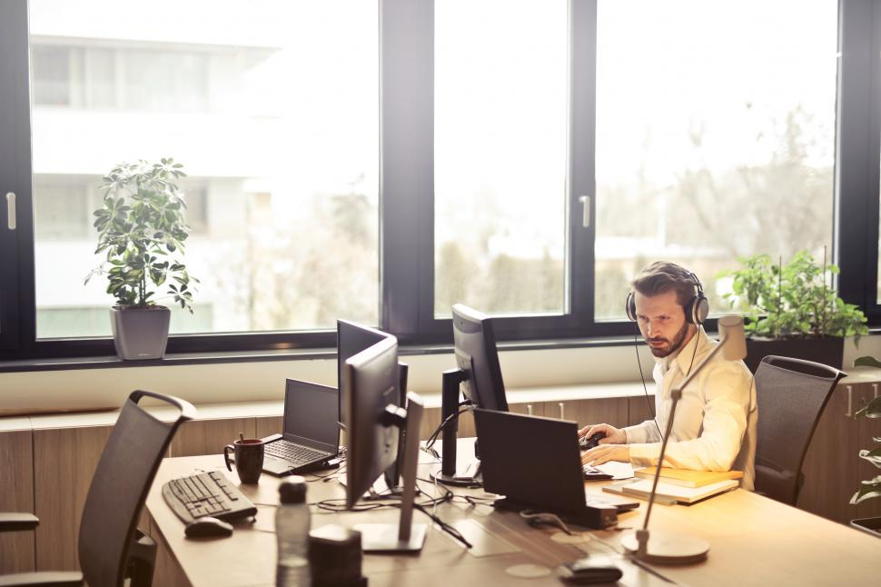Download Free Stock HD Photo of Young Man working at computer while listening music with headpho Online